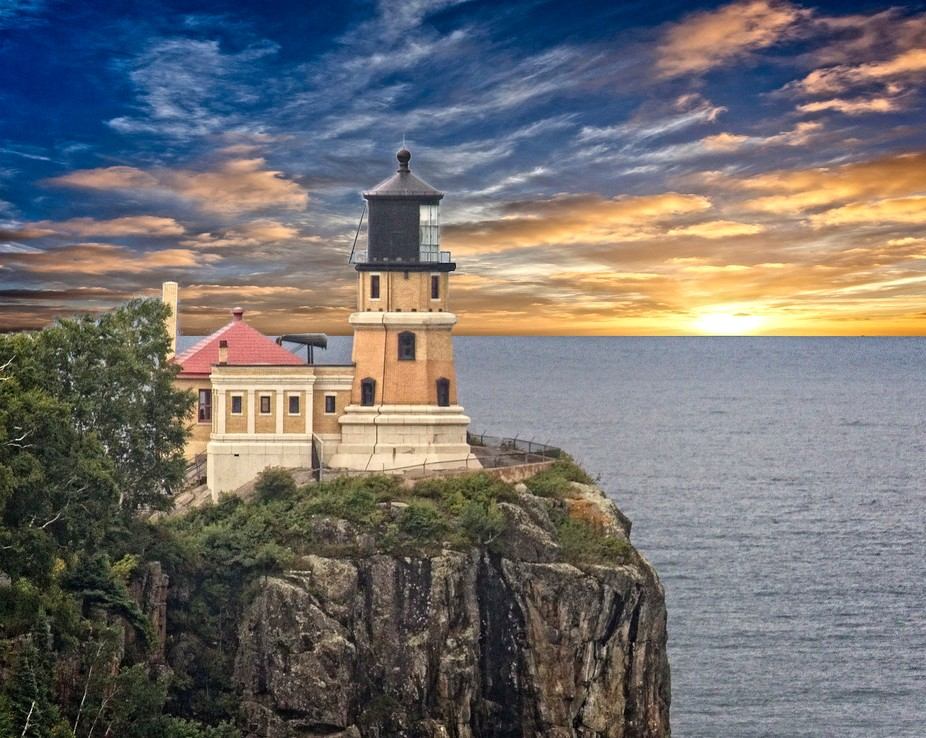 On a bluff lookin out on  Lake Superior sits a proud lighthouse.  The varied colors of the sky en...