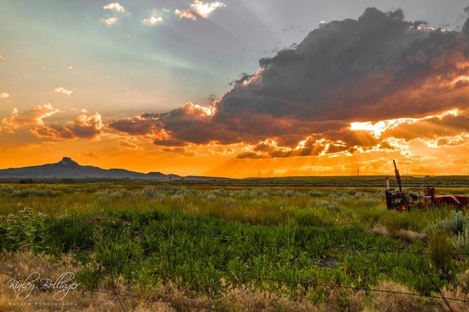 Sunsets, tractors, mountains, and fields make this image an embodiment of the Wyoming way of life.