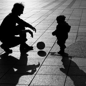 Man and boy paying with ball in the street