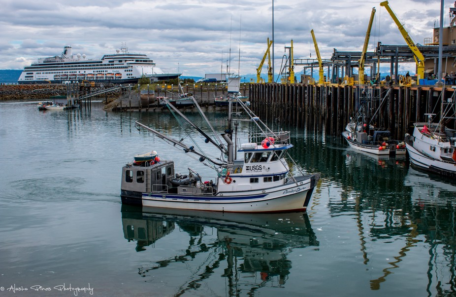 A USGS fishing boat came in to port to off load at the harbor, while a cruise ship waits in the background for their passengers.