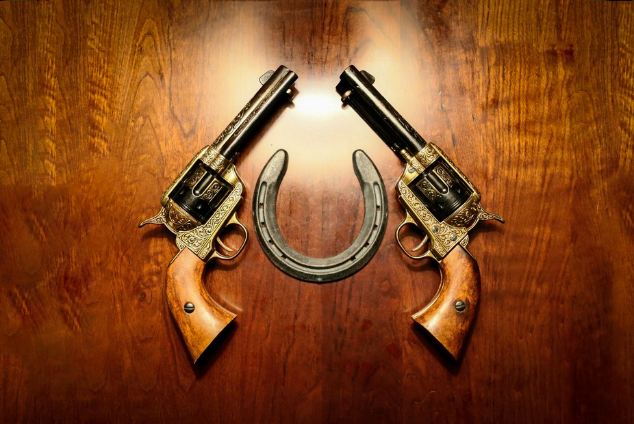 Old west pistols with horse shoe on a cherry wood background