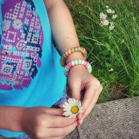 A photo of my daughter holding a daisy