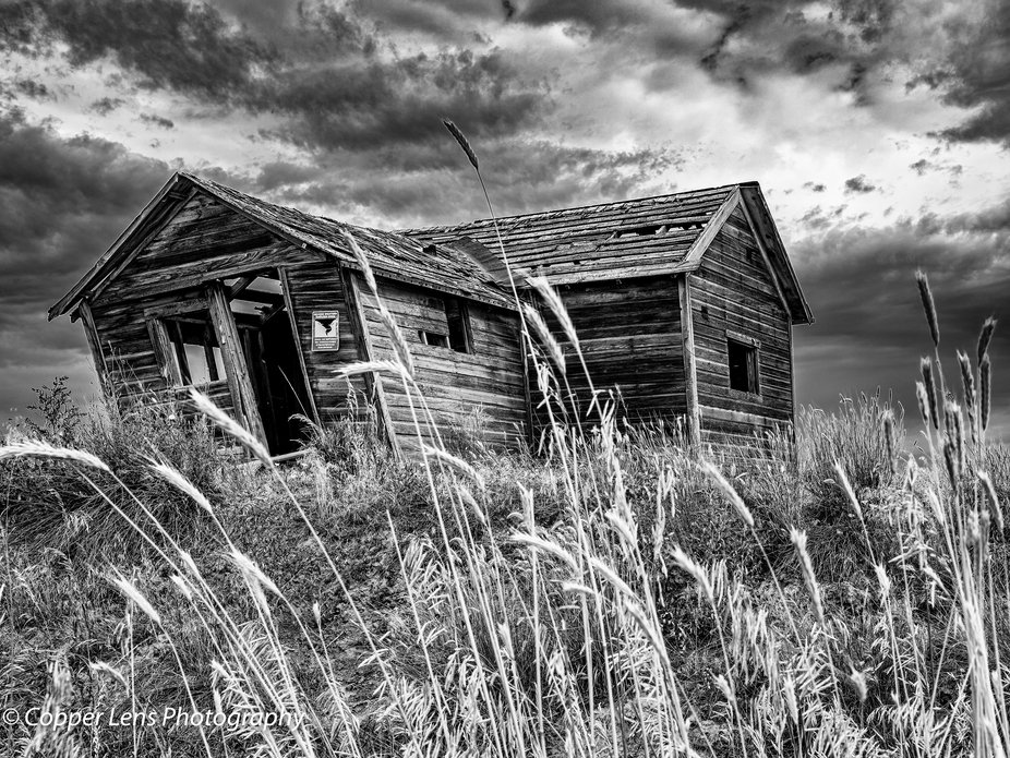 Abandoned home in Weld County Colorado with a tornado shelter sign on it