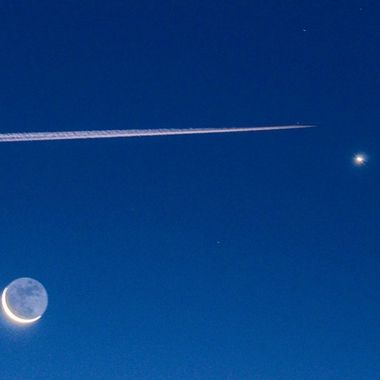 A jet plane whites up the sky and the moon and jupiter are visible in the night sky