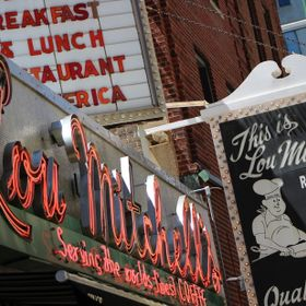 """Lou Mitchell's Restaurant And Bakery Chicago"" is an angled photograph of the Lou Mitchell's Restaurant & Bakery signs in..."
