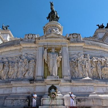 View from the street of Altare della Patria in Rome.  In the lower portion of the center of the frame is an eternal flame, guarded by soldiers.