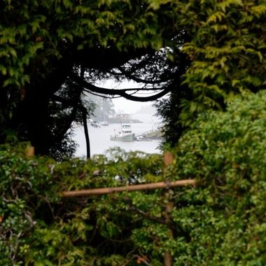 A view through the hedge at Butchart Gardens to the harbor.