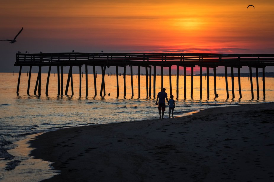 sunrise along the Chesapeake Bay as father and son take a walk