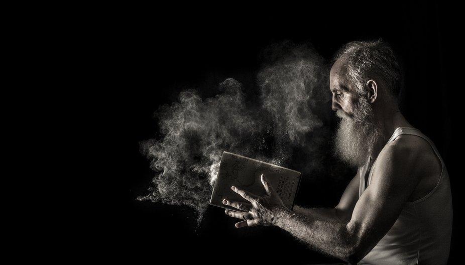 Man slamming a book shit. Dust appears