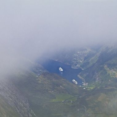 I took this photo during our boat trip to the Norwegian Fjords. We were travelling by bus on the Stryn Mountains. This photo was taken right at the top of the mountains (1500 metres) amongst the clouds. I waited about an hour for the clouds to disperse to take this photo of the Geiranger Fjord.