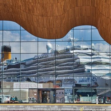 I took this photo during our boat trip to the Norwegian Fjords. This photo was taken in   the town of Kristiansand. We were walking infront of the opera building where I noticed the reflection of our ship, the Costa Favolosa, on the building. This was the result.