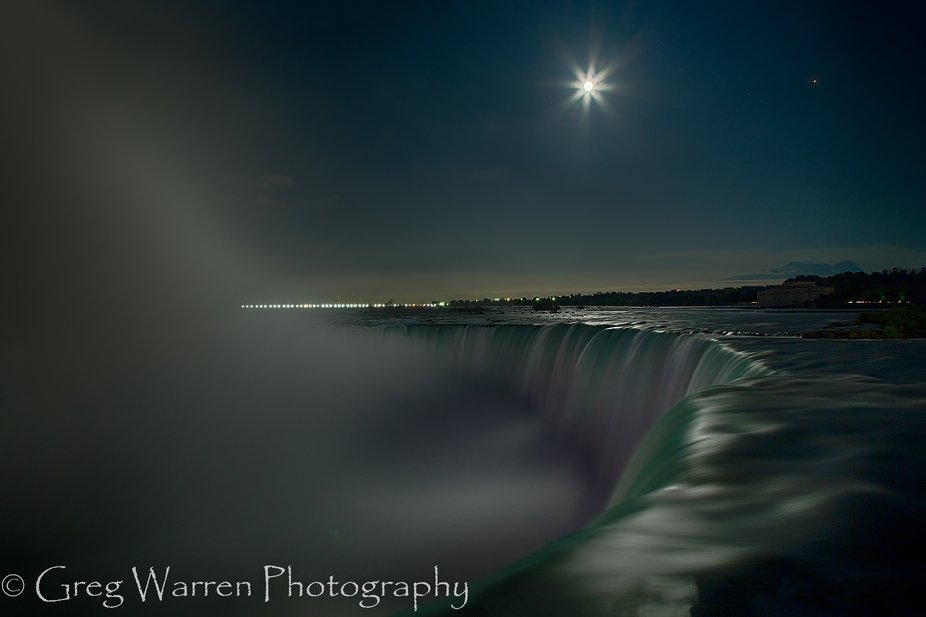 Niagara Falls under a full moon, with Mars appearing as a red dot in the sky