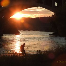 A sunset taken under an arch of the Rt 462 Susquehanna river bridge with a fisherman silhouetted in the foreground