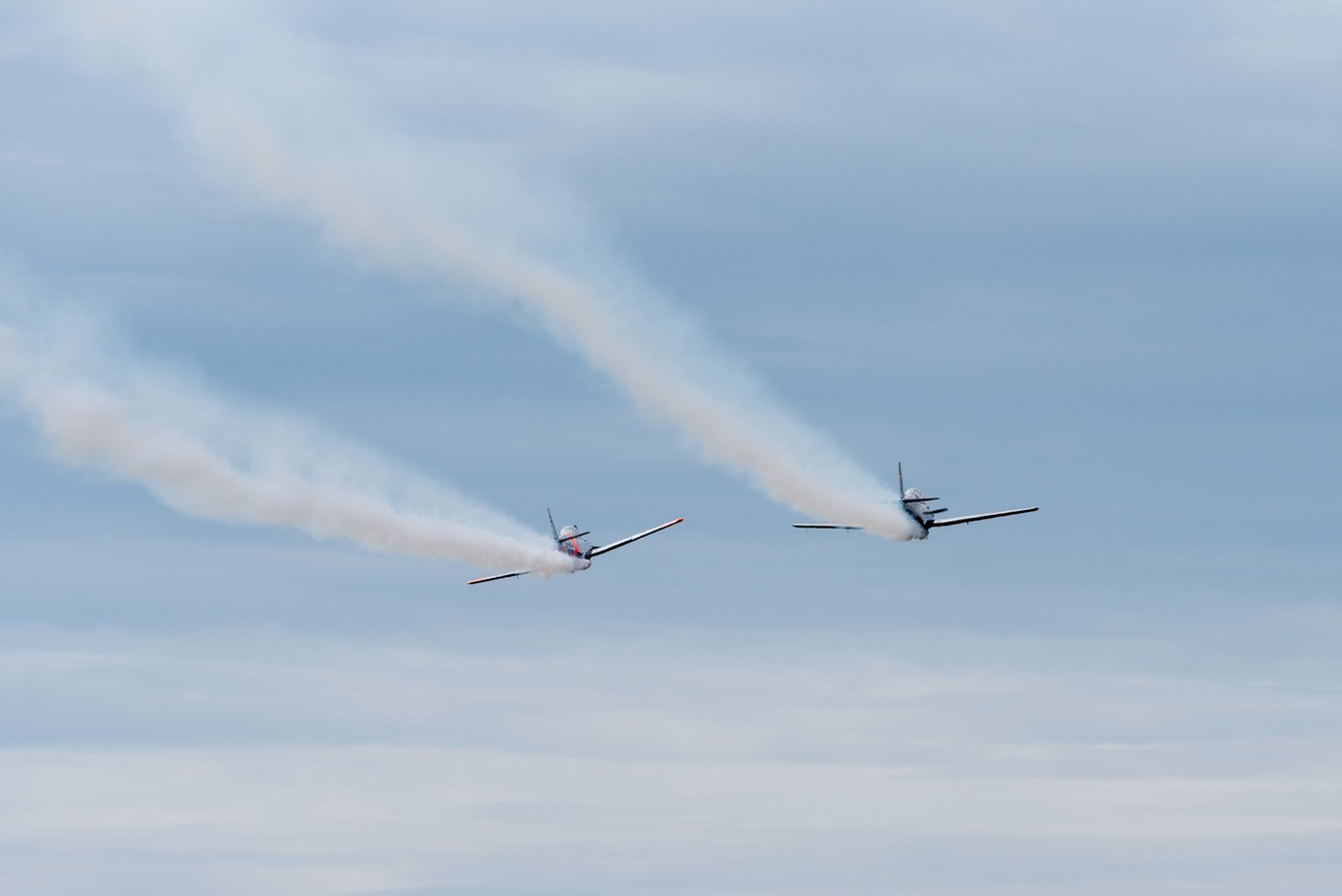 2 planes blowing smoke at a local airshow