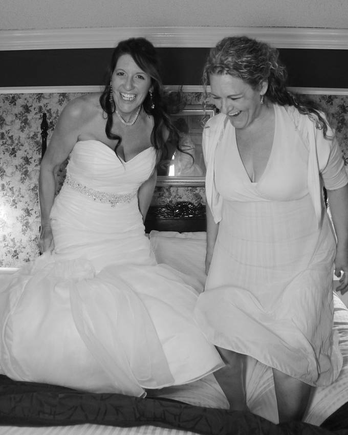 Two sisters though adults are children at heart, jumping on a bed together so happy to be in that moment.