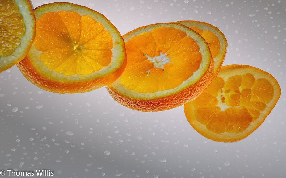 A sliced orange in mid-air.