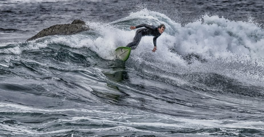 A surfer dodges rocks as he rides the waves near Carmel, California