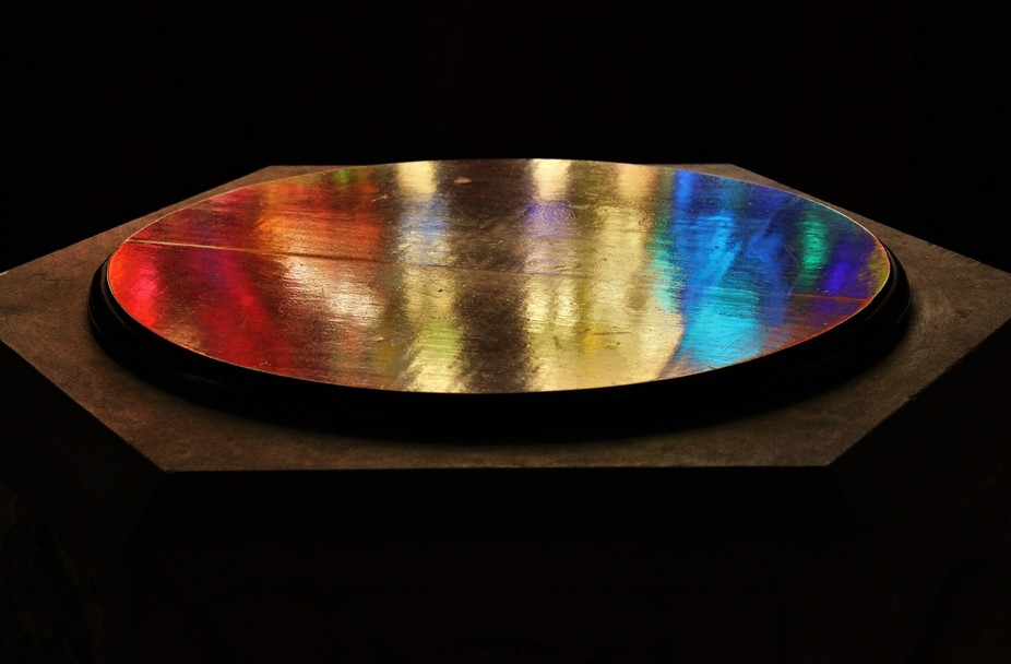 A photo I took today of light from a stained glass window reflected on the wooden surface of a ba...