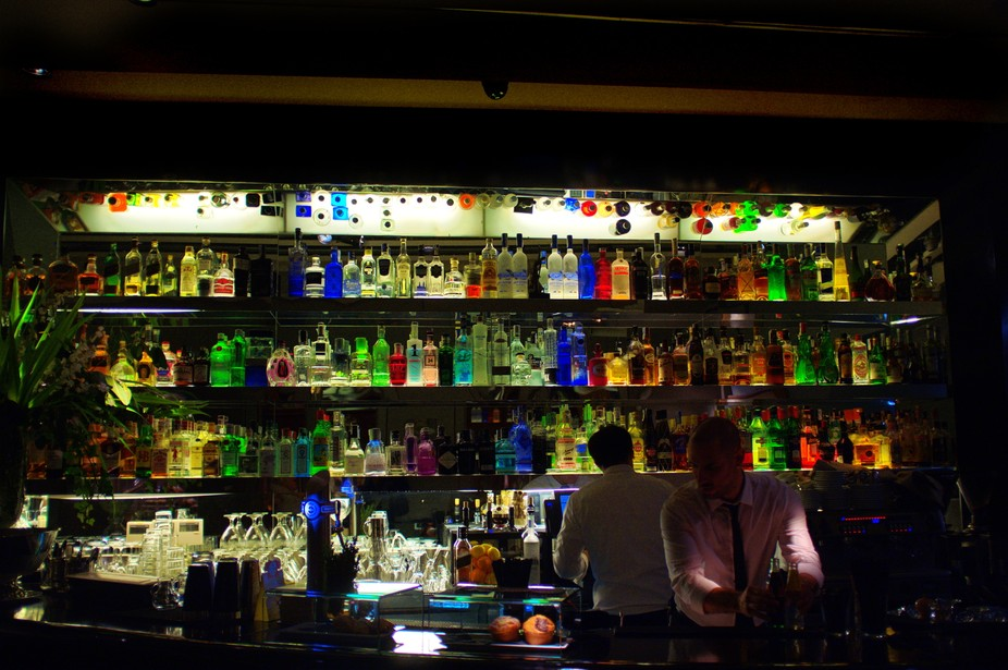 A colorful bar with many bottles in the background