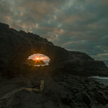 The sun sets through the arch in the north coast of Tenerife (Spain)