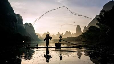 Cormorant fisherman casting net