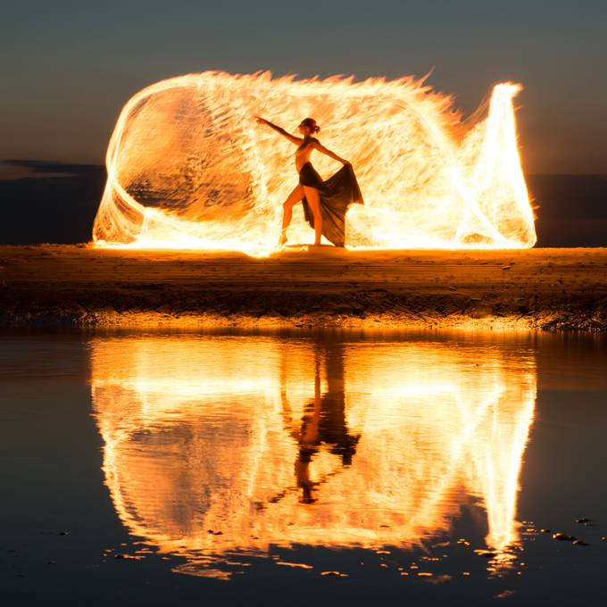 Night session with light painting on the beach with Aria Rainbow (Model Mayhem # 3786685). An oil-soaked burning kevlar rope was moved during a long exposure while the model remained motionless.  20180717 198