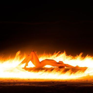 Night session with light painting on the beach with Aria Rainbow (Model Mayhem # 3786685). An oil-soaked burning kevlar rope was moved during a long exposure while the model remained motionless.
