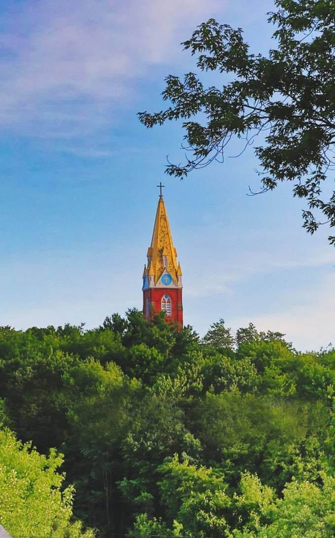 The steeple of this church glistens in the sunset , towering over the trees