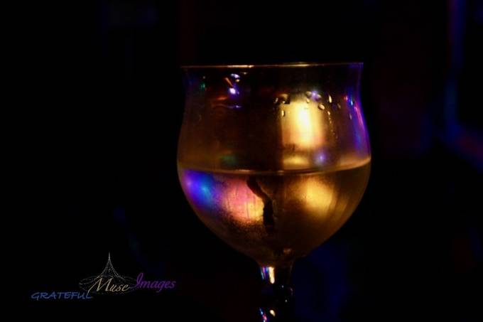 Colored lights reflecting in a frosty wine glass.