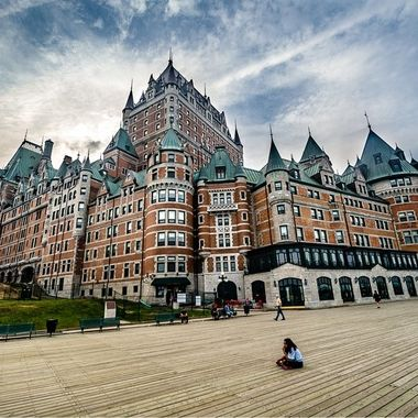 "The Château Frontenac was designed by American architect Bruce Price, as one of a series of ""château"" style hotels built for the Canadian Pacific Railway company (CPR) during the late 19th and early 20th centuries; the newer portions of the hotel—including the central tower (1924)—were designed by Canadian architect William Sutherland Maxwell. CPR's policy was to promote luxury tourism by appealing to wealthy travellers. The Château Frontenac opened in 1893, six years after the Banff Springs Hotel, which was owned by the same company and is similar in style."