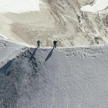 Ice climbers crossing a narrow arête on a ridge approaching the Aiguille du Midi high above Chamonix, Mont Blanc.