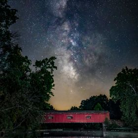 Reflected in the waters of Owen County, Indiana's Mill Creek, Cataract Covered Bridge is topped by the Milky Way on a clear summer night.