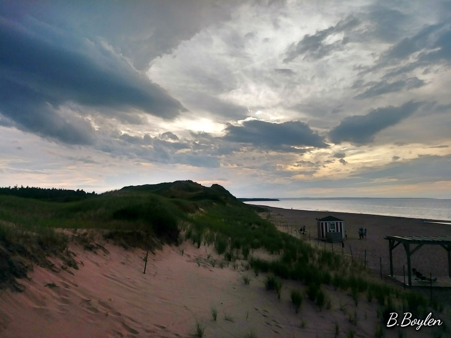 The sand dunes of Brakley's shores kissed by the tufts of grass you see sprinkled atop t...