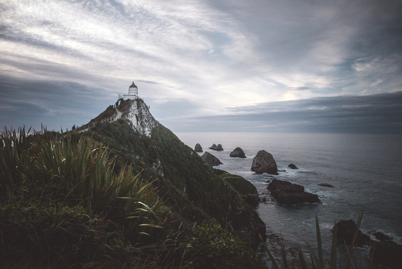 The nugget point lighthouse is an iconic New Zealand lighthouse and scenic lookout. Sunrise is often epic on the ocean's horizon behind the famous nugget rocks.