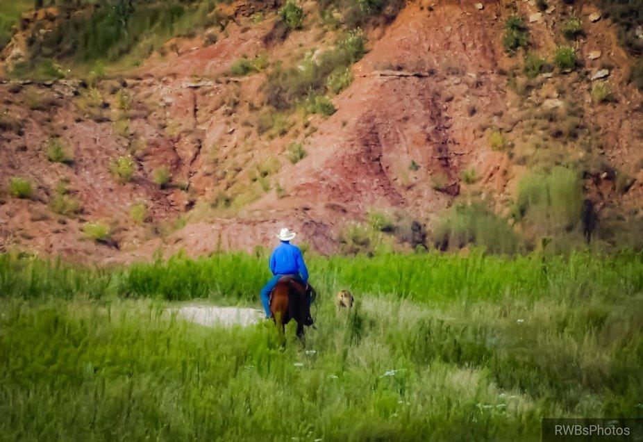 Cowboy unaware at foot of Gypsum Hills