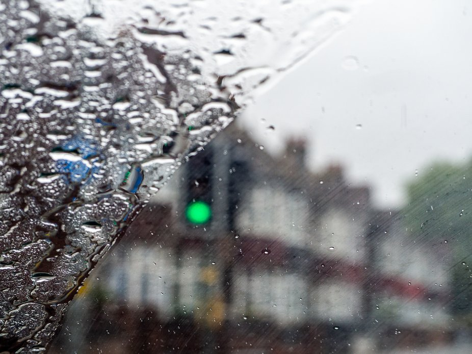 Green traffic lights through a rainy windscreen.