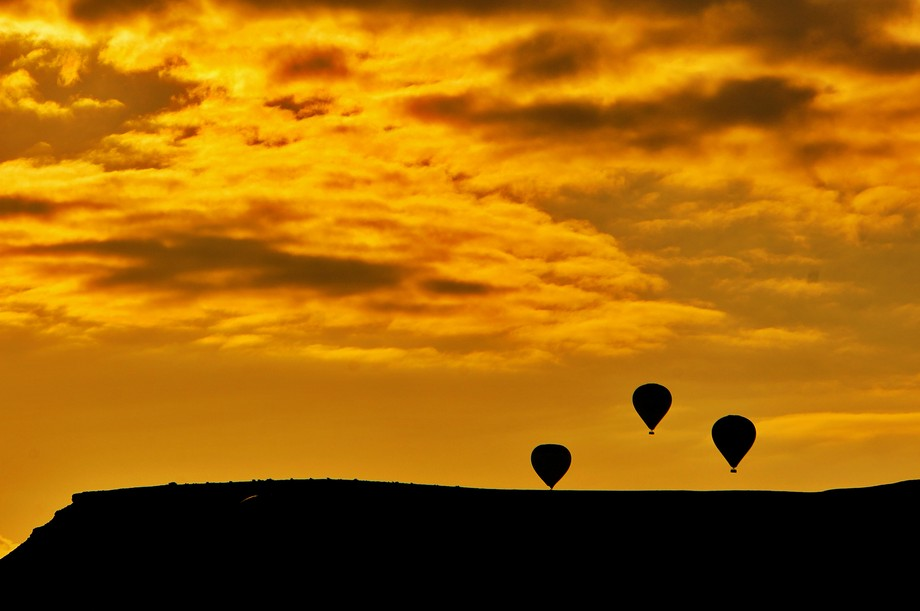While the sun rises in Kapadokya, it's famous air balloons start getting airborne to app...