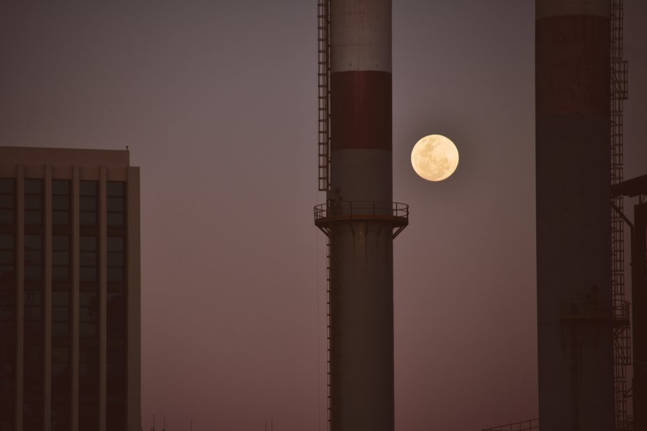 The full moon passing by the chimneys of a power plant.