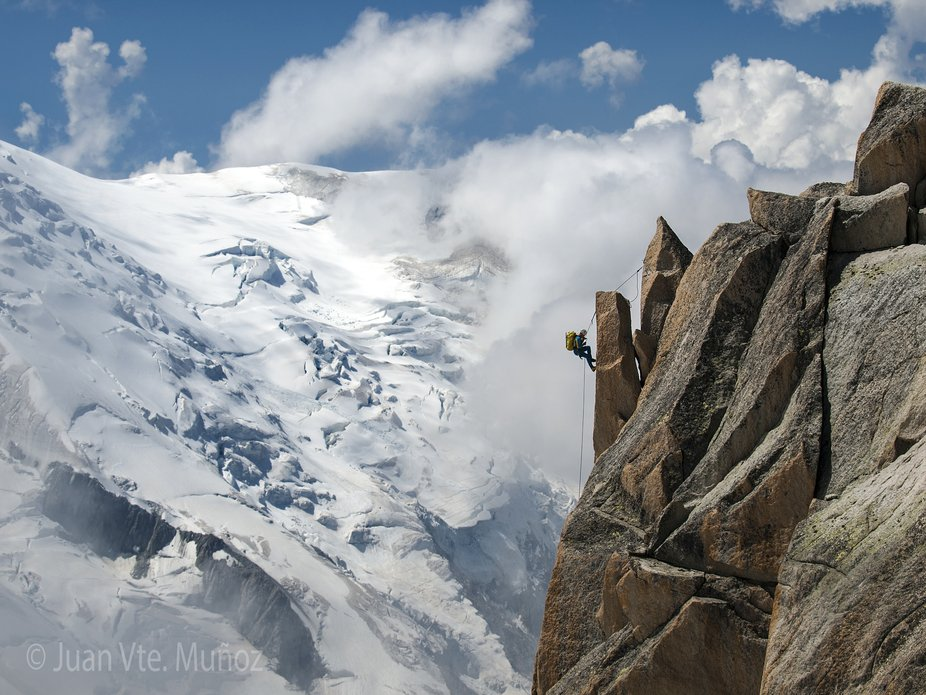 A climber descending a rock wall with the Mont Blanc glacier in the background. This photo was ta...