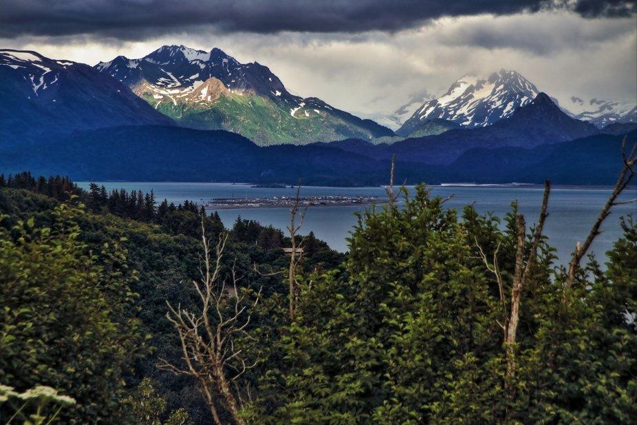 A peek of sun illuminates a peak on the Kenai Mountains; the end of the Homer (Alaska) Spit sits ...