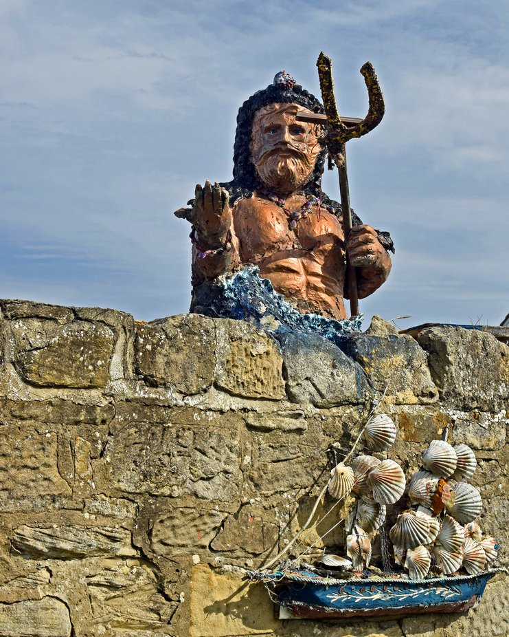 King Neptune peering over his garden wall. Taken at the Kings Head in Seaton Sluice Northumberland  UK.