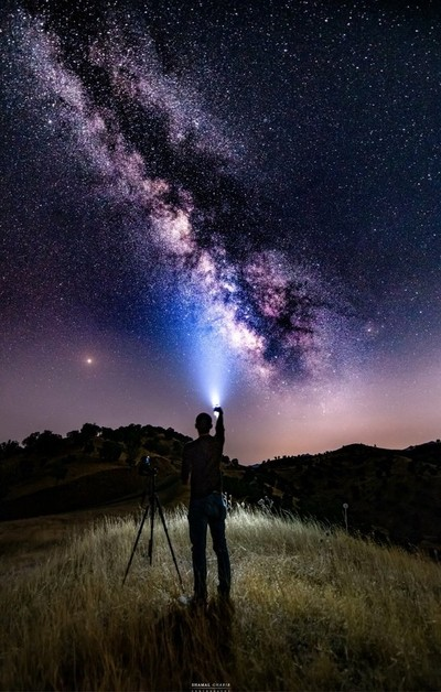 milky way with photographer in the middle of the night