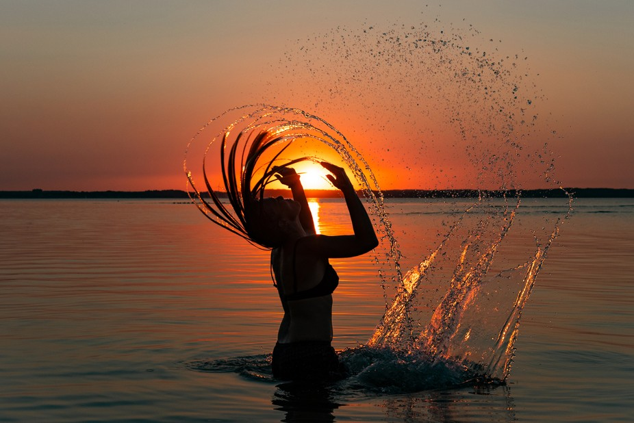 Holding the sunset in your hands while playing with the sea water