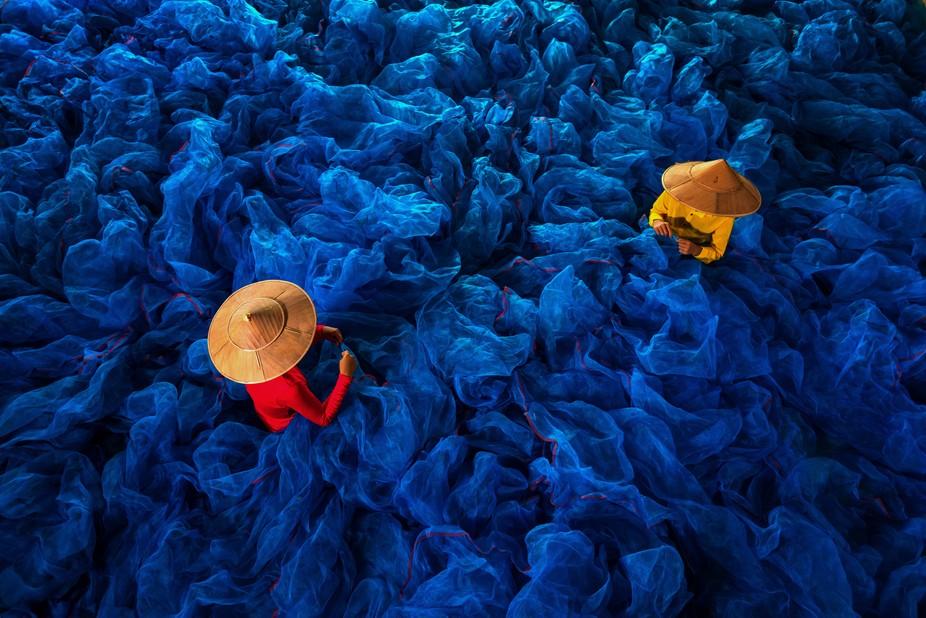 Two girls are making fishing net in Myanmar.