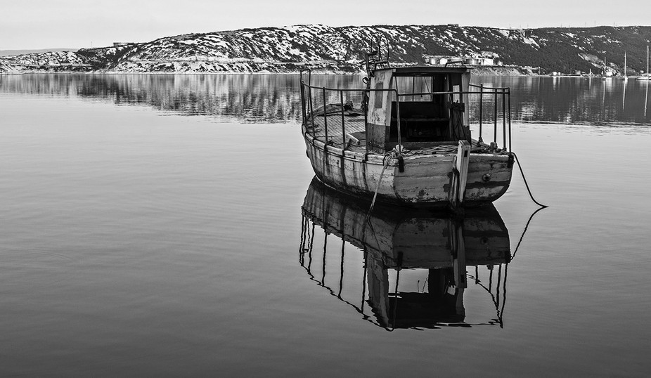 An old and tired fishing boat in dawn ...