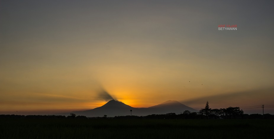Sunset rays between Mount Merapi (left) and Mount Merbabu (right), Indonesia