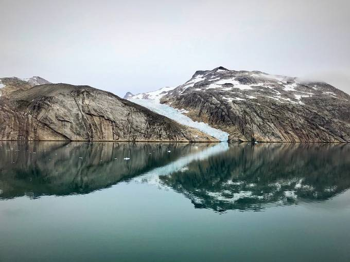The smiling man lying in the water of the glaciated fjords of Greenland.  by mykalrand - Lakes And Reflections Photo Contest