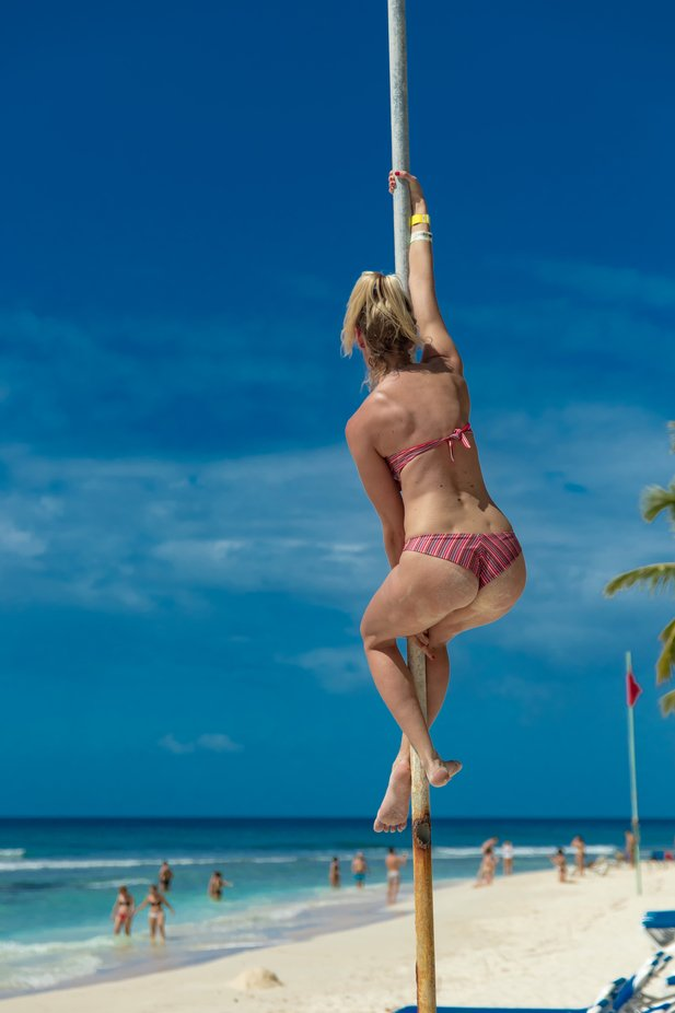 In a hot day, a spicy real vision on the beach while people enjoy relax. She was on the pole, observing the natural beauty of Caribbean sea and showing the bauty of her  bottom curves...