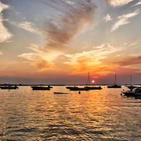 A great sunset at little boathouse in a shallow sea of Porto Casareo, Salento