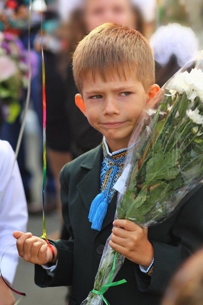Funny first year student with flower bouquet at his first school day.